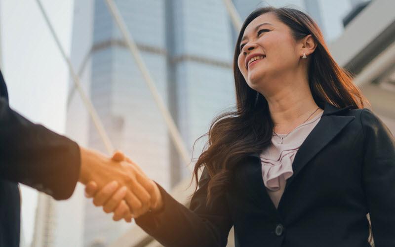 Asian business women in black suit handshake - Logistics Institute of Singapore (LIS)